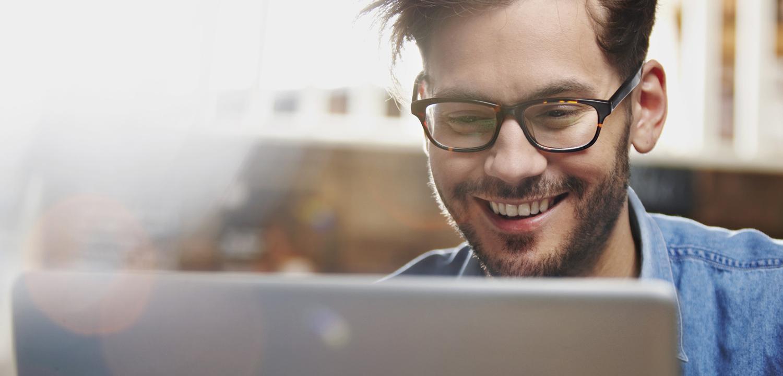 homem sorrindo trabalhando de óculos software sistema desenvolvimento fábrica de códigos Marília SP
